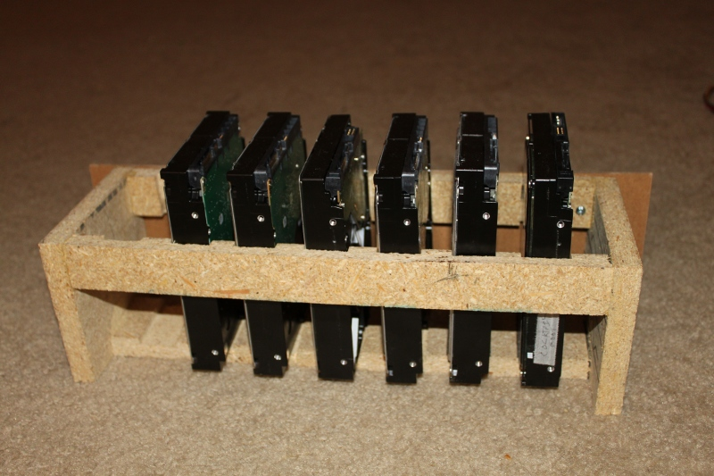 A simple, slotted wooden cage for 7 hard drives